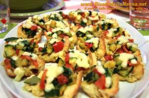 Tartine in crosta di pane con zucchine, pomodoro e mozzarella